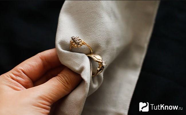 Девушка держит кольца с камнями в вафельном полотенце