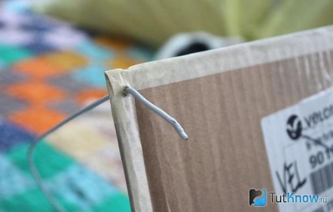 Продетая сквозь картон проволока