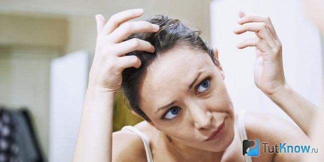 Девушка осматривает волосы на своей голове