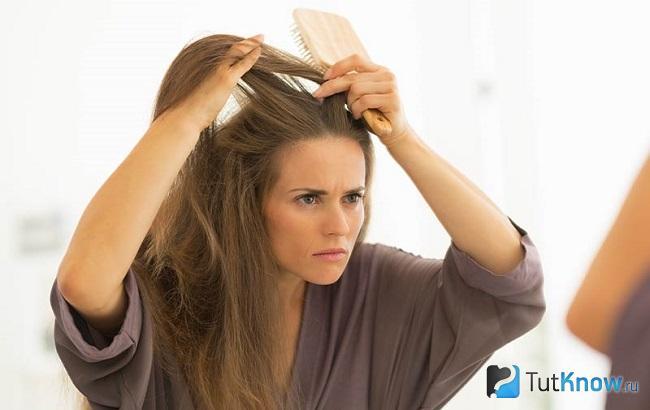 Женщина осматривает пряди своих волос