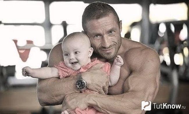Культурист держит на руках ребенка