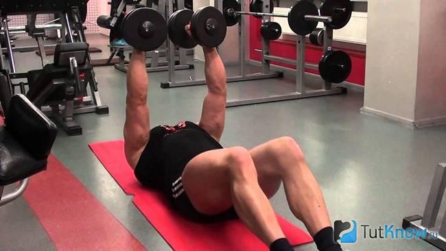Спортсмен выполняет жим гантелей, лёжа на полу
