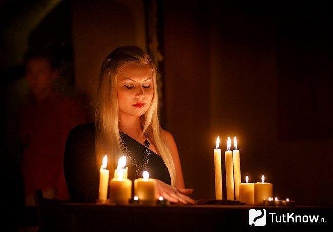 Молодая девушка занимается гаданием при свечах
