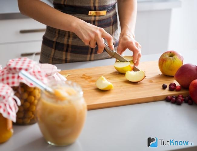 Женщина режет яблоки на повидло